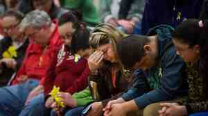 Residents bow their heads during a prayer service Friday at Haller Middle School in Arlington, Wash., that was dedicated to the communities affected by the Highway 530 mudslide.