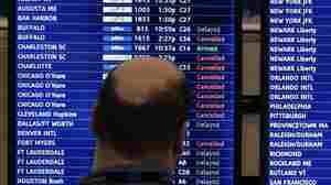 A man looks at a flight departure board filled with weather-related cancellations and delays at Boston's Logan Airport in January.