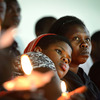 Rwandan women hold candles during a night vigil and prayer for genocide victims at Amahoro stadium.