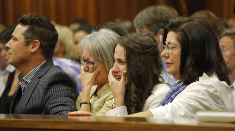 Aimee Pistorius (second from right) cries as she hears her brother Oscar speak Tuesday during his murder trial in Pretoria, South Africa, about the night he killed