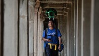 A Cambodian technician carries a backpack-mounted