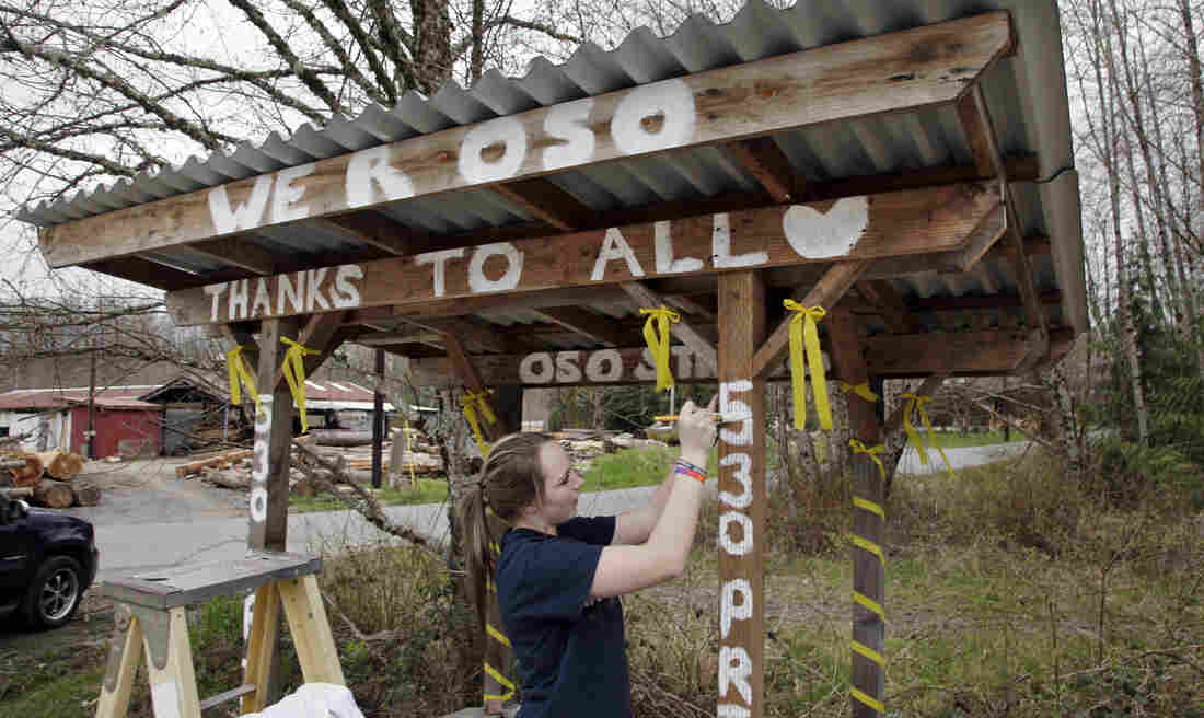 Tayler Drayton, 16, finishes painting words of support on a bus stop on Thursday for those affected by a deadly mudslide.