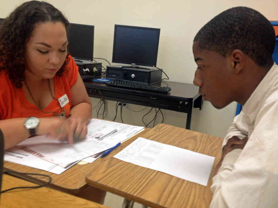 Student Mack Godbee and mentor Natasha Santana-Viera go over Godbee's report card. Godbee's performance has improved since a data monitoring program identified him as a dropout risk.