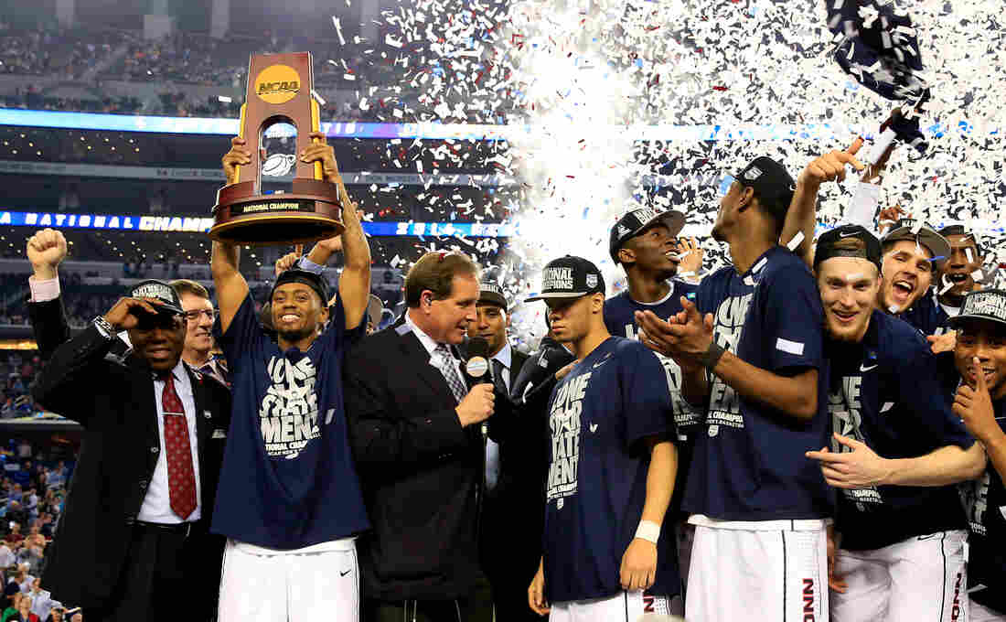 Ryan Boatright of the Connecticut Huskies holds up the NCAA championship trophy after defeating the Kentucky Wildcats 60-54 at AT&T Stadium on Monday, as his teammate Shabazz Napier is interviewed after the game.