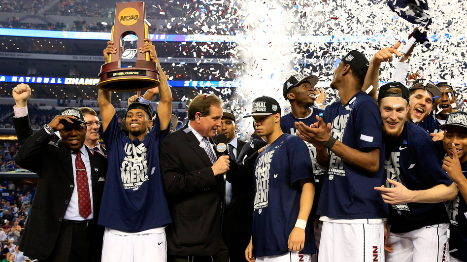 Ryan Boatright of the Connecticut Huskies holds up the NCAA championship trophy after defeating the Kentucky Wildcats 60-54 at AT&T Stadium on Monday, as his teammate Shabazz Napier is interviewed after the game. (Getty Images)