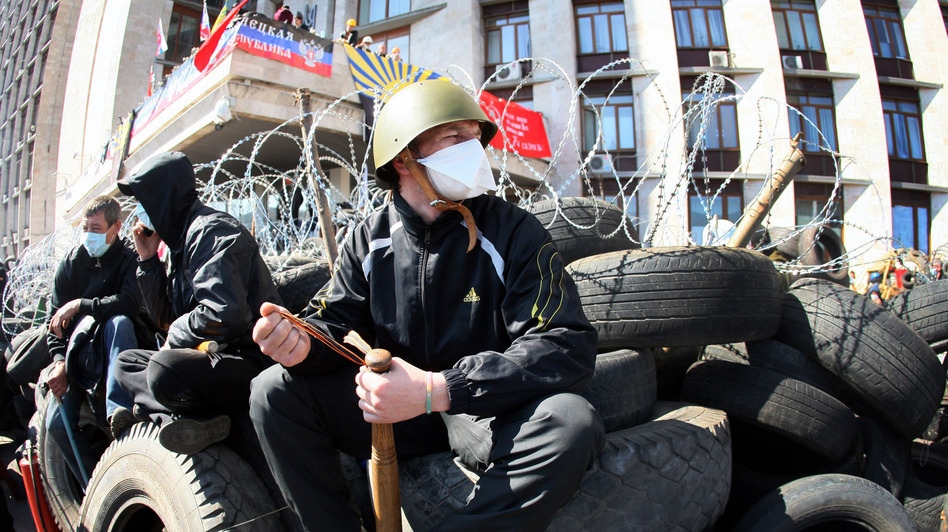 A pro-Russian militant holding a bat guards a barricade in front of the Donetsk Regional Administration building on Tuesday. (AFP/Getty Images)