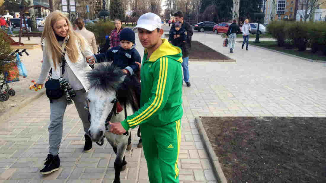 """Emir Gushinov (in green) says not many children are taking his pony rides in Donetsk nowadays. But he said that's not because of the unrest nearby. """"The main reason is that it's not a holiday,"""" he says."""