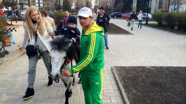 "Emir Gushinov (in green) says not many children are taking his pony rides in Donetsk nowadays. But he said that's not because of the unrest nearby. ""The main reason is that it's not a holiday,"" he says. (Ari Shapiro/NPR)"