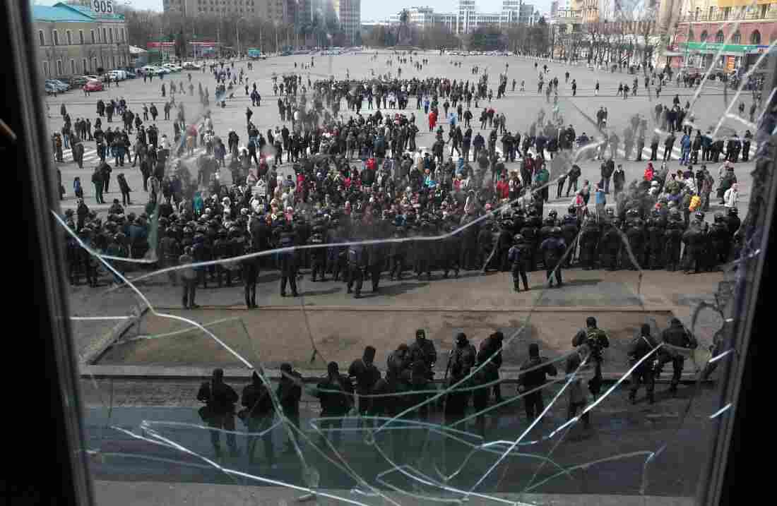 A photo taken through a shattered window shows pro-Russian protesters in front of Ukrainian police guarding the Kharkiv regional state administration building Tuesday.