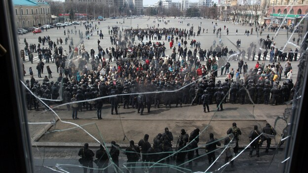 A photo taken through a shattered window shows pro-Russian protesters in front of Ukrainian police guarding the Kharkiv regional state administration building Tuesday. (AFP/Getty Images)