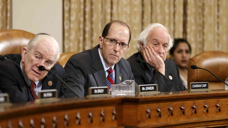 House Ways and Means Committee Chairman Rep. Dave Camp, R-Mich. (center), flanked by the committee's ranking member, Sander Levin, D-Mich. (right), and Sam Johnson, R-Texas, listen on Capitol Hill April 9 as the panel debates whether IRS official Lois Lerner's refusal to testify to Congress deserves criminal prosecution.