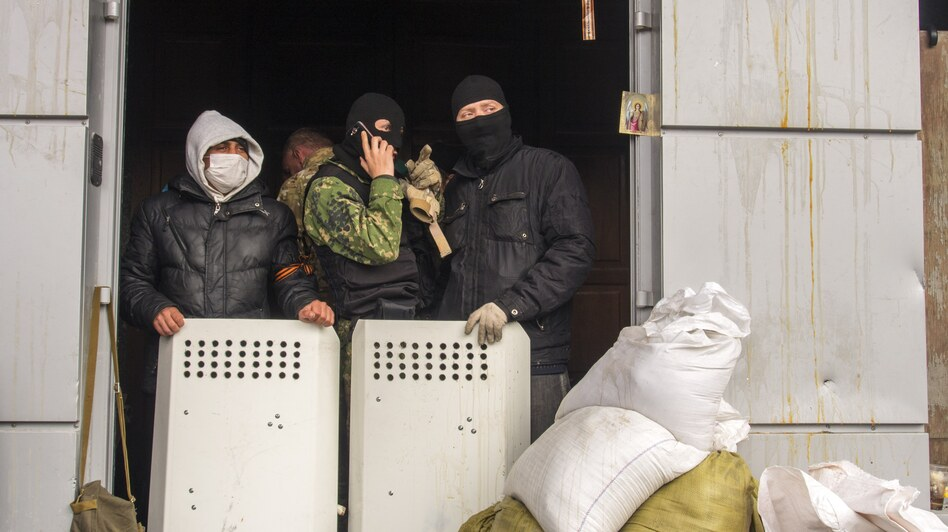 Masked pro-Russia activists guard an entrance to the Ukrainian regional office of the Security Service in Luhansk, 20 miles west of the Russian border, in Ukraine, on Wednesday. (AP)
