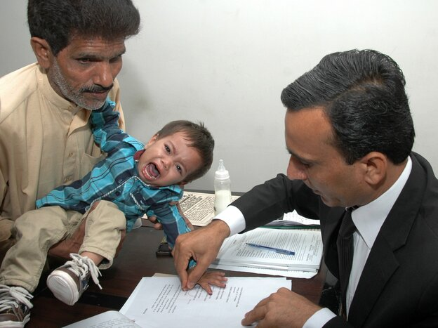 A Pakistani lawyer takes the thumb impression from 9-month-old Musa Khan on a bail bond in Lahore, on April 3.
