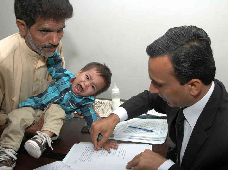A Pakistani lawyer takes the thumb impression from 9-month-old Musa Khan on a bail bond in Lahore, on Ap