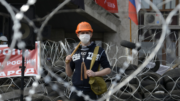 A pro-Russia protester stands at a barricade outside a regional government building in Donetsk, Ukraine, on Wednesday. (Reuters/Landov)