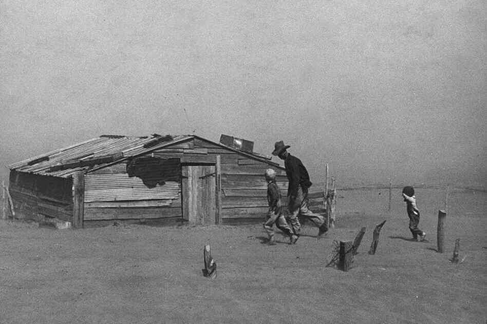 "Father and sons walk through a dust storm in Cimarron County, Okla. (1936) Steinbeck writes: ""The dust was evenly mixed with the air, an emulsion of dust and air. Houses were shut tight, and cloth wedged around doors and windows, but the dust came in so thinly that it could not be seen in the air, and it settled like pollen on the chairs and tables, on the dishes."""