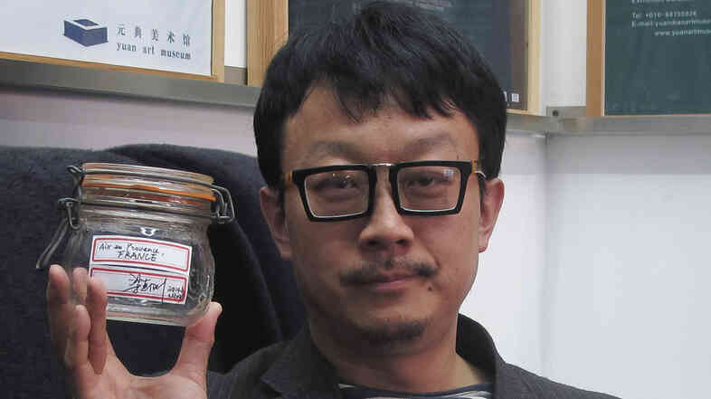 Beijing artist Liang Kegang poses in a Beijing art gallery earlier this week with the jar of fresh air he collected in Provence, France.