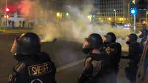 Riot police launch tear gas toward activists in downtown Albuquerque, N.M., last month following a 10-hour protest around the city, in response to a deadly police shooting.