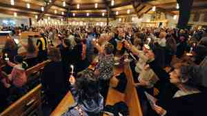 At Mother of Sorrows Catholic Church in Murrysville, Pa., on Wednesday evening, worshipers held candles as they prayed for those injured in a stabbing attack at the local high school.