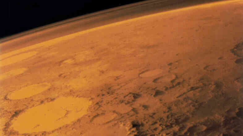 This Viking 1 orbiter image shows the rocky surface and thin atmosphere of Mars.