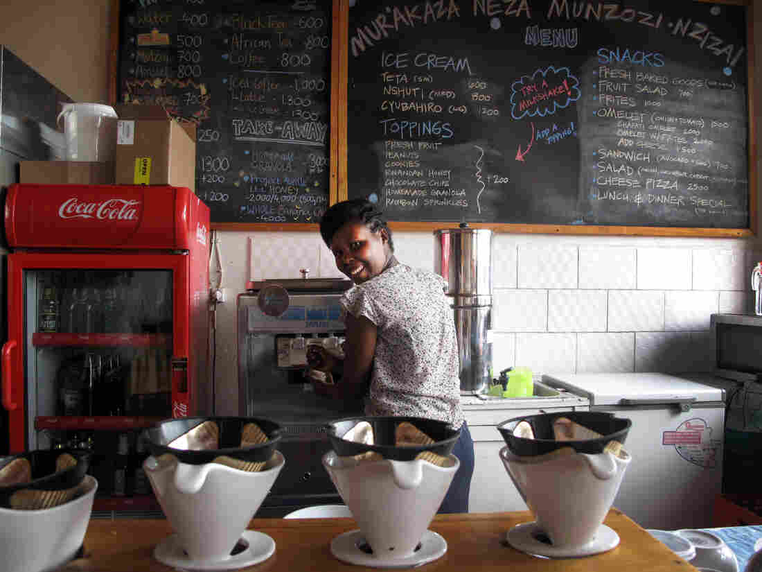 """Manager Louise Ingabire fills an order for Belgian chocolate/banana swirl. """"We were the first women drummers in Rwanda, and now we're the first to bring ice cream,"""" she says. """"We would like to change the culture."""""""