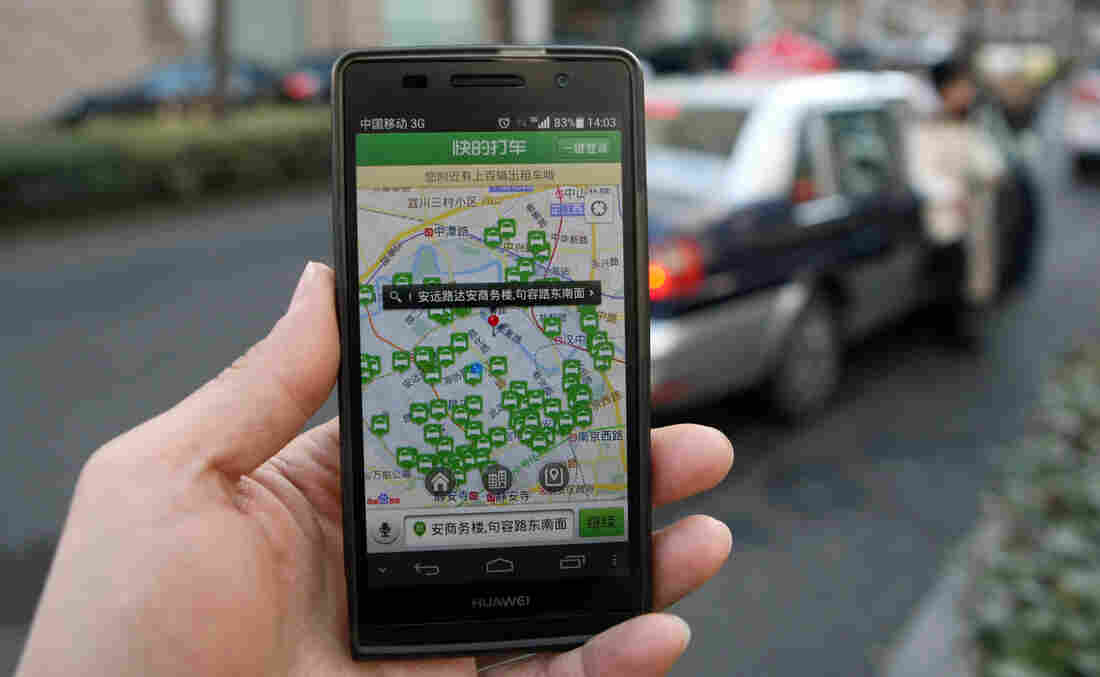The Shanghai government has banned the use of taxi-booking apps such as Kuaidi Dache during rush hour. Here, a Shanghai resident displays the app on his smartphone in Shanghai, on Jan. 23.