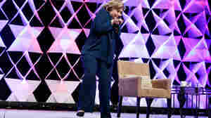 Former Secretary of State Hillary Clinton ducks after a woman threw a shoe at her while she was delivering remarks at the Institute of Scrap Recycling Industries conference on Thursday in Las Vegas.