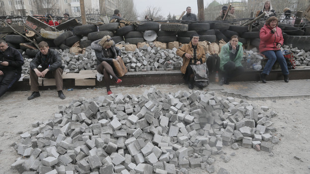 Pro-Russian activists sit at a barricade at the regional administration building in Donetsk on Wednesday. Police have been conspicuously absent at Eastern Ukraine protest sites. (AP)
