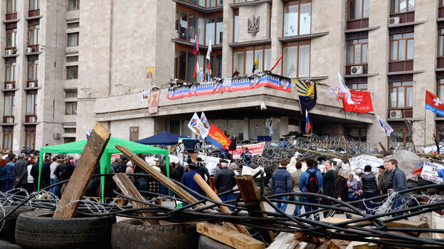 Pro-Russian protesters surround a barricade made by used tires and barbed wire Friday in Donetsk, Ukraine. Pro-Russian protesters took control of the government building and have held it since Sunday.
