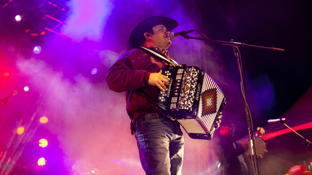 Ricky Munoz, lead singer of Intocalbe, performs in Juarez, Mexico earlier this month. Intocable, a band popular on both sides of the border, is inspired by Mexican music, country hits and rock bands like Def Leppard. (Kainaz Amaria/NPR)