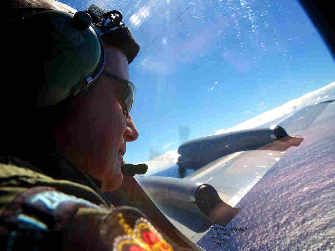 Sgt. Trent Wyatt looks out an observation window on Friday from aboard a Royal New Zealand air force P-3 Orion maritime search aircraft as it flies over the southern Indian Ocean. So far there's been no sign of Malaysian Airlines Flight 370. But officials are hoping that sounds detected below the surface are coming from one or both of the plane's black boxes.
