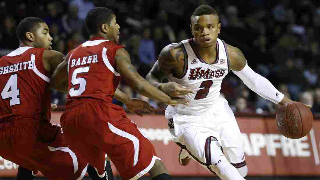 Massachusetts' Derrick Gordon (No. 2) drives past Northern Illinois' Dontel Highsmith (No. 4) and Travon Baker (No. 5) during an NCAA basketball game in Amherst, Mass., on Dec. 14.