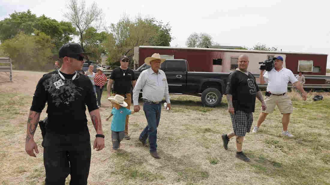 Rancher Cliven Bundy (center) walks with his grandson Braxton Louge along with armed security guards near his ranch house Friday. Bundy's ranch, west of Mesquite, Nev., has become a rallying point for protesters who back his fight against the Bureau of Land Management over grazing fees.