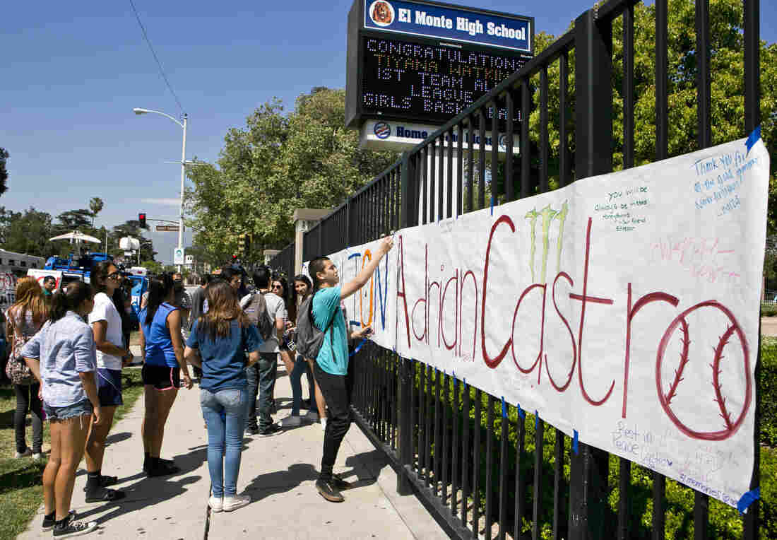 El Monte High School students hang a banner for senior Adrian Castro outside their school Friday. Castro was killed when the Humboldt State University-bound bus he was on crashed in Orland on Thursday, an El Monte school official said.