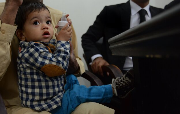 Pakistani toddler Mohammad Musa, seen here sitting in his grandfathe