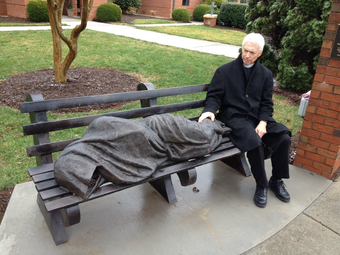 The Rev. David Buck sits next to the Jesus the Homeless statue that was installed in front of his church, St. Alban's Episcopal, in Davidson, N.C.