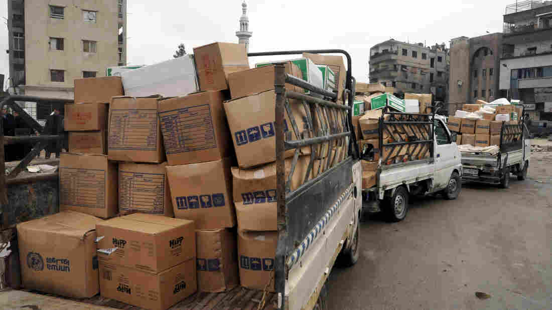 Trucks carrying U.N. supplies arrive at the besieged Yarmouk refugee camp on the southern edge of Damascus, Syria, in February. According to the World Food Programme, it costs $41 million a week to meet the country's food needs.