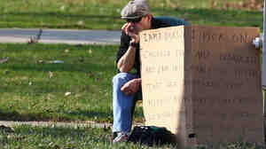 """Edmond Aviv, 62, sits with a sign at a street corner in the Cleveland suburb of South Euclid Sunday. Aviv, who called his neighbor """"monkey momma"""" as she held her adopted, disabled African-American children, was ordered by a judge to display the sign."""