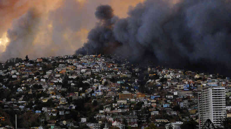 Smoke fills the sky behind a hill in Valparaiso, Chile, Saturday. The large fire burned through the night and is blamed for at least 11 deaths.