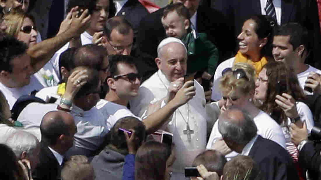Pope Francis poses for pictures with the audience after Palm Sunday service in St. Peter's Square at the Vatican Sunday.