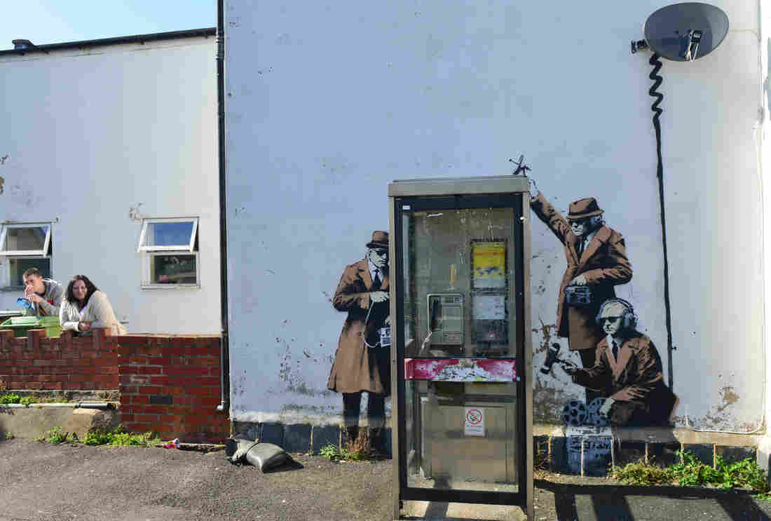 Suspected Banksy artwork appears on the side of a house, depicting government agents spying on a phone box near GCHQ (Government Communications Headquarters) in Gloucestershire, England, Sunday.