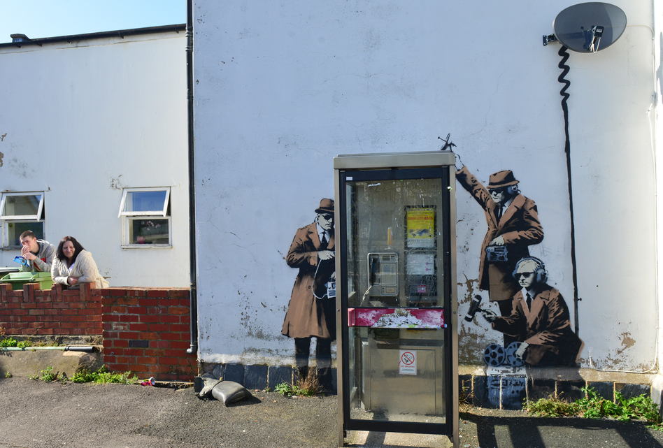 Suspected Banksy artwork appears on the side of a house, depicting government agents spying on a phone box near GCHQ (Government Communications Headquarters) in Gloucestershire, England, Sunday. (Jules Annan/Barcroft Media/Landov)