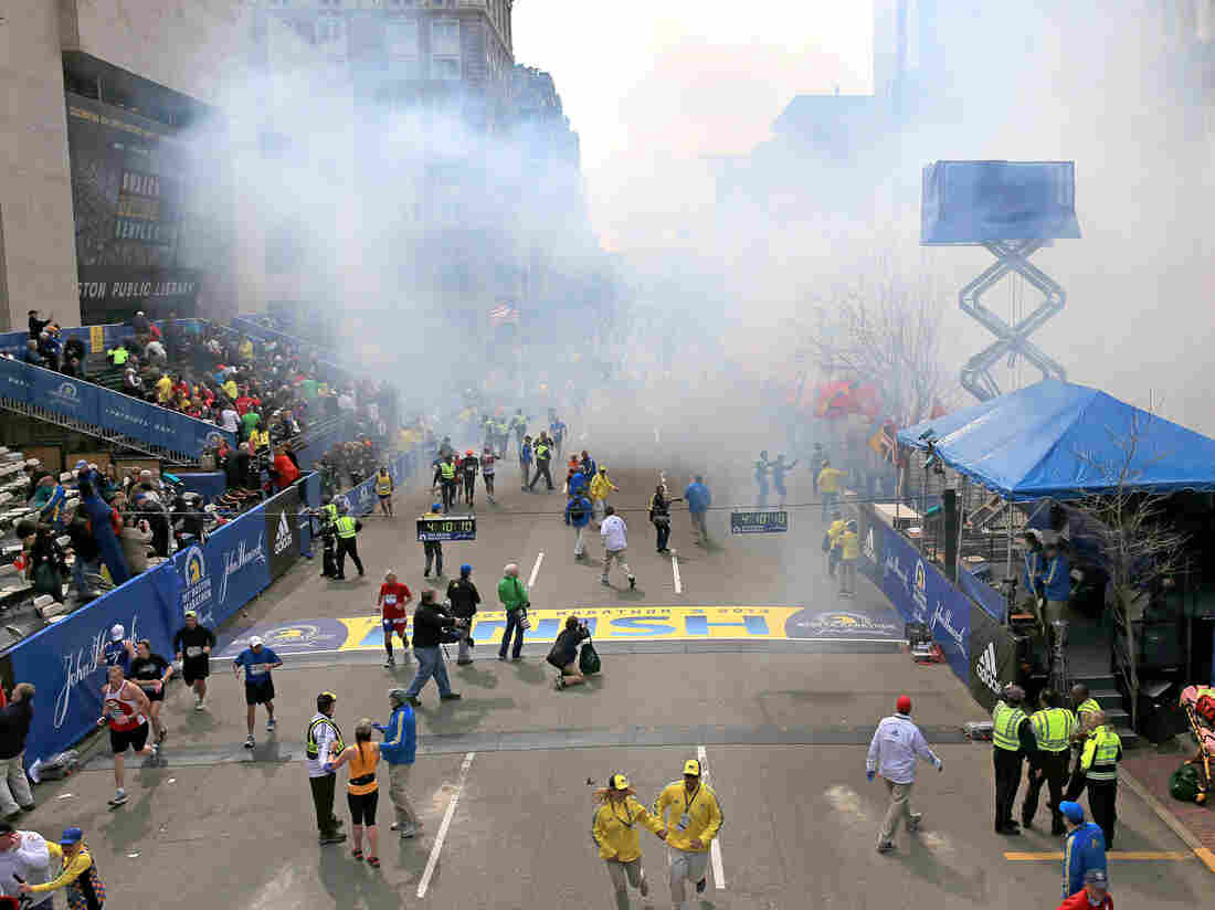 The Boston Marathon finish line moments after two bombs exploded on April 15, 2013. With the race clock reading 4:10:10, Demi Clark can be seen in the bottom left (orange-yellow top, braided hair, black tights) telling two race officials that she had to get to her family in the stands.