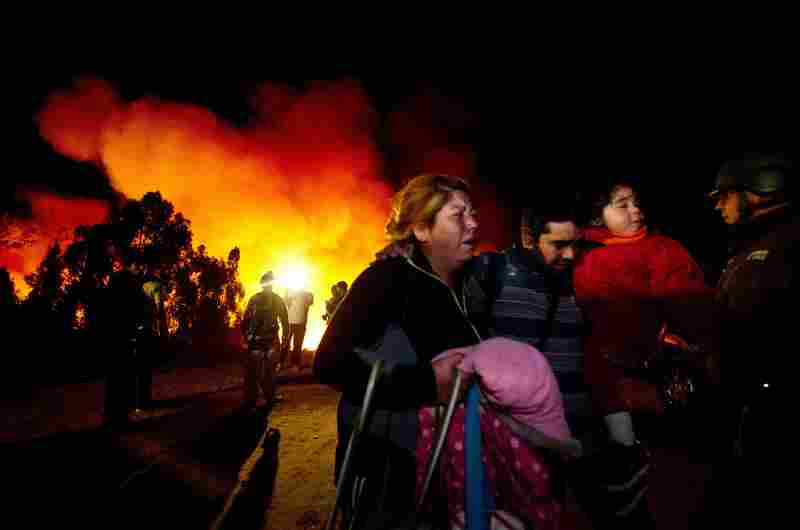 People flee after a fire reactivated in Valparaiso, Chile, Sunday. More than 10,000 people were evacuated as an army of firefighters battled the killer blaze.