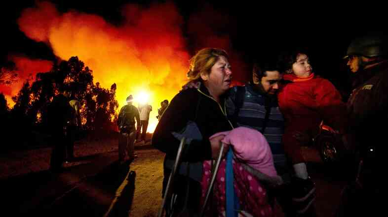 People flee after a rejuvenated fire threatened their neighborhood in Valparaiso, Chile, Sunday. More than 10,000 people have been evacuated because of the fire.