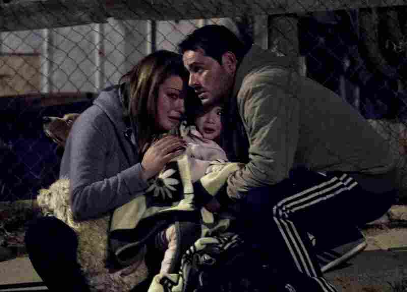 A couple and their baby take temporary refuge after a large fire flared up in their district of Valparaiso, Chile, Sunday. More than 10,000 people were evacuated as an army of firefighters battled the blaze.