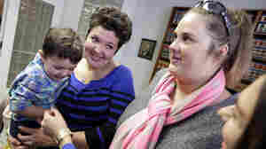 Nicole Yorksmith (left) holds her son while standing with her partner, Pam Yorksmith. They were among four legally married couples who filed a federal civil rights lawsuit seeking to compel Ohio to recognize same-sex marriages on birth certificates.