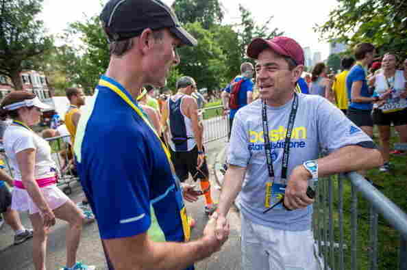 Boston Marathon race director Dave McGillivray (right) greets runners during the Boston Athletic Association 10K race in Boston last year.