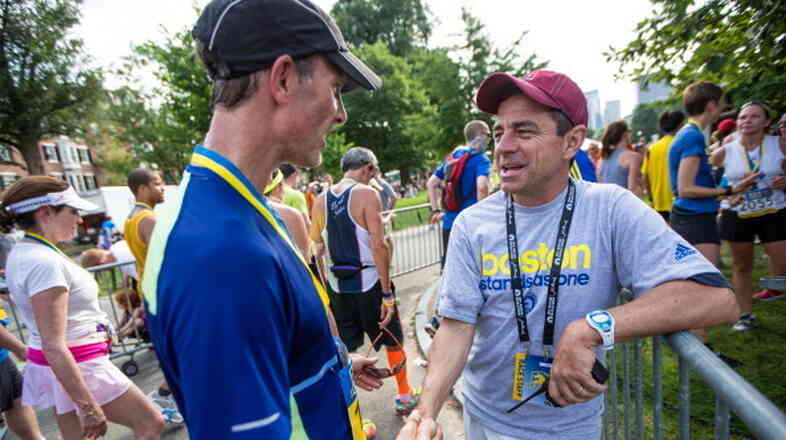 Boston Marathon race director Dave McGillivray (right) greets runners during the Boston Athletic Association 10K race in Boston.