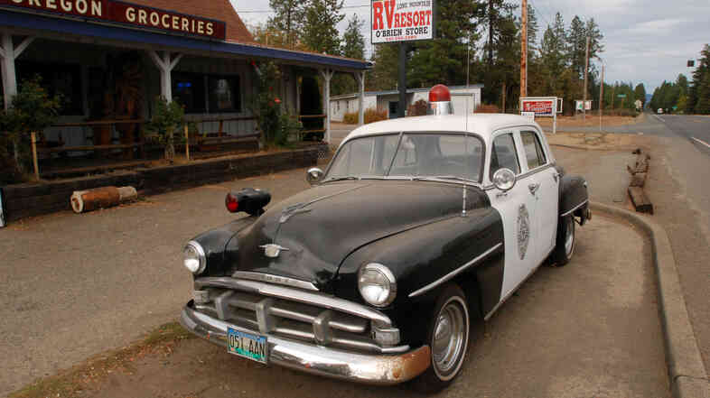An old police car is permanently parked on the highway through O'Brien, Ore., where cuts to the sheriff's office have prompted some locals to mount armed patrols.